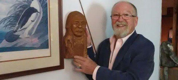 a  chiropractor holding a wooden sculpture