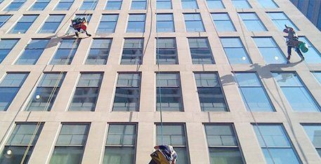 Window cleaners on outside of office building