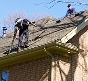 Workers up on the roof of a house