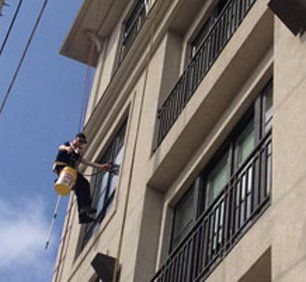 Window cleaner working from harness and rope