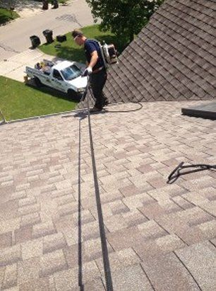 Worker up on roof of house cleaning gutter