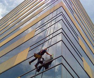 Window cleaner at work on outside of building