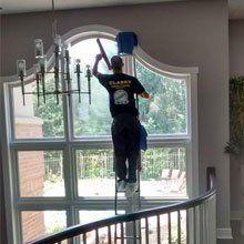 Window cleaner up on ladder cleaning inside of large residential window