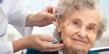Inserting hearing aid in senior's ear