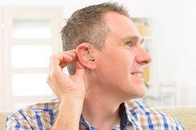 Man showing deaf aid
