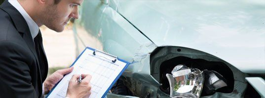 Man assessing auto damage