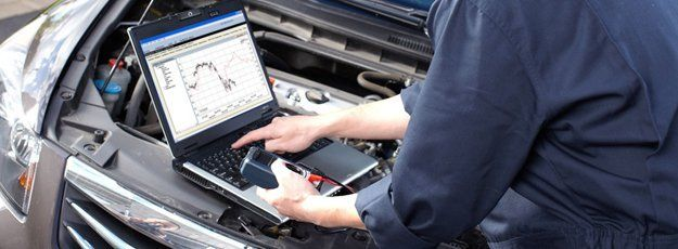 Mechanic using computer to check engine