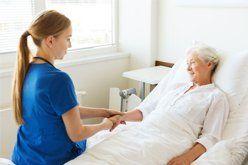caregiver holding hands of senior woman