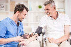 male caregiver checking blood pressure of senior citizen