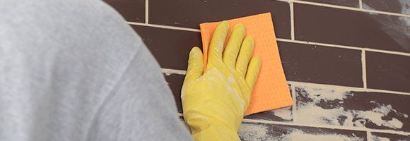 yellow-gloved hand cleaning grout with sponge