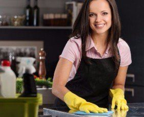 smiling young woman in yellow gloves and brown apron cleaning kitchen counter