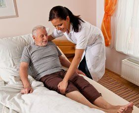 female nurse assisting elderly man into bed with white comforter