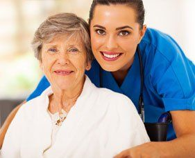 nurse leaning over shoulder of smiling elderly woman in wheelchair