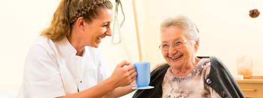 caregiver holding coffer cup while laughing with an elderly female client