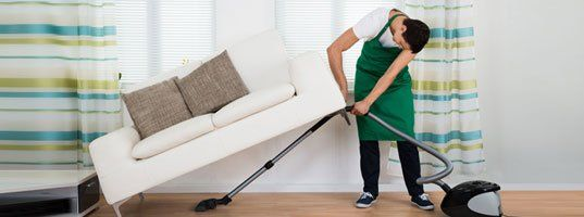 caregiver in green apron lifting corner of couch to vacuum underneath