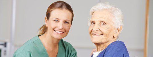 smiling nurse and elderly patient