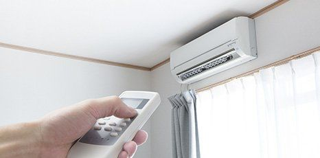 a person holding a controller for air conditioner