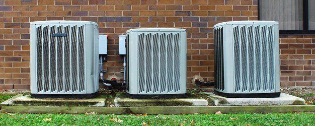 three HVAC units outside a house