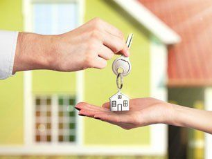 Handing over house key with a house background