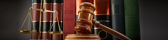 scales of justice and gavel in front of leather bound books