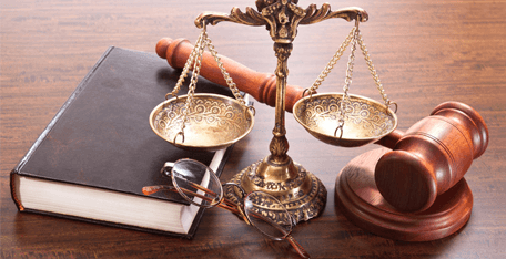 Scales of justice, gavel, and leather bound book on desk