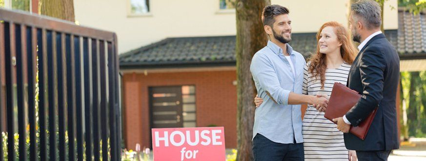 Couple and an agent infront of their new house