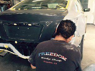 man in branded t-shirt repairs bumper