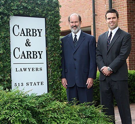 image of two men, one older and other younger, in suits, standing next to ivy covered sign that reads