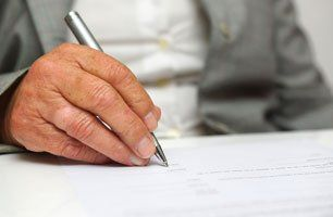 close up of hand holding a silver ballpoint pen, writing on a form