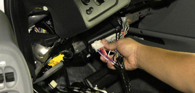 man working on car wiring