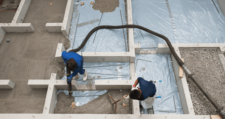 Two workers pouring concrete from hose and spreading it with rake