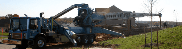 Concrete pumping truck with extended boom in residential site