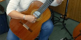 teacher Sharon Whitinghill playing acoustic guitar in classroom