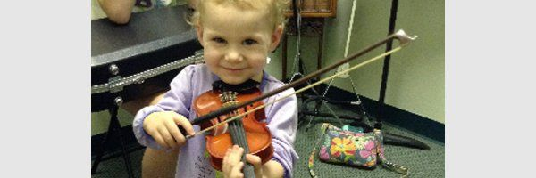 very young female child playing a violin and smiling