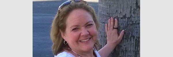 Smiling teacher Carol Thomas standing with hand on tree
