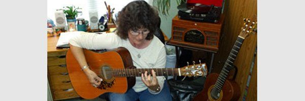 teacher Sharon Whittinghill with acoustic guitar