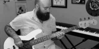 teacher Patrick Goble in black and white picture playing a bass guitar