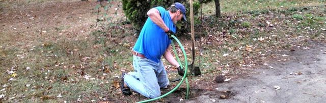 Worker in yard with house flushing residential sewer main