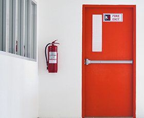 hand held firs extinguisher hanging on wall next to fire exit