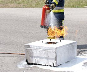 firefighter using hand-held fire extinguisher on test fire