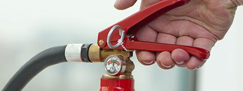 close-up of fire extinguisher handle, valve, hose, and release pin