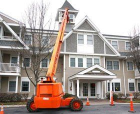 orange crane in front of house