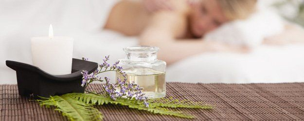Candle, massage oil and flowers for spa decoration