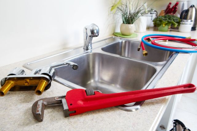 new faucet and pipe wrench laying on sink counter