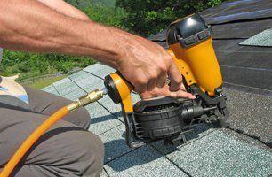 Roof contractor repairing roof shingles