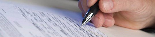 close-up of hand holding a ball point pen over a contract