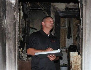man inspecting the burnt house