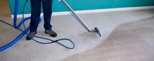 worker vacuuming the water damaged carpet