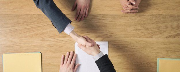 clients shaking hands with lawyer