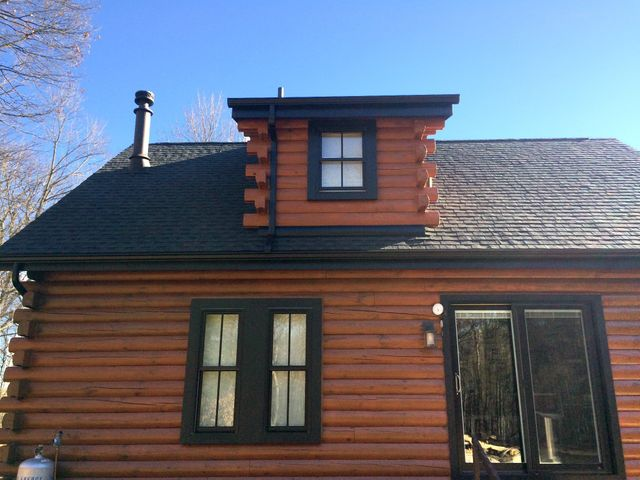 wooden house with black roof and black gutters